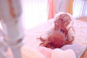 枕と写真でおまじないする女の子